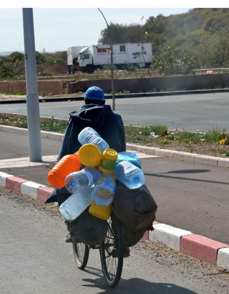 Mannen samlar vattenflaskor